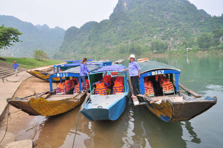 mugla: Quang Binh, Vietnam - October 23, 2015: Traditional local boats transfered for tourism are mooring at a pier waiting for travellers