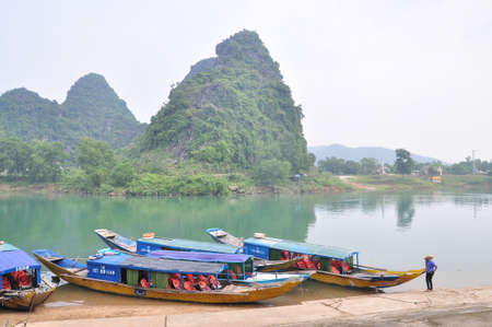 Quang Binh, Vietnam - October 23, 2015: Traditional local boats transfered for tourism are mooring at a pier waiting for travellers