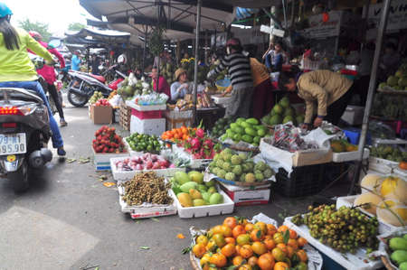 scamper: Nha Trang, Vietnam - February 7, 2016: Plenty of fruits and grocery are for sale in a street market in Vietnam Editorial