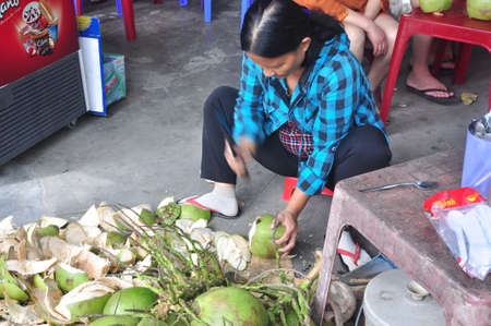 Nha Trang, Vietnam - February 7, 2016: A Vietnamese woman is cutting coconut for travellers on a treet vendor