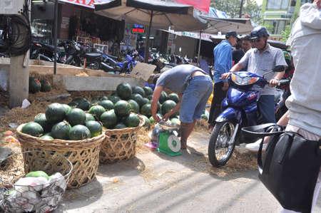 merchant: Nha Trang, Vietnam - February 7, 2016: Plenty of watermelon are for sale in a street market in Vietnam Editorial