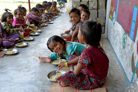 gurgaon: New Delhi, India - October 5, 2015: Children are having a healthy meal at Mobile Creches, Vatika-83, Gurgaon, Delhi. Mobile Creches works with birth to 12 year old children living on the construction sites and slums since 1969