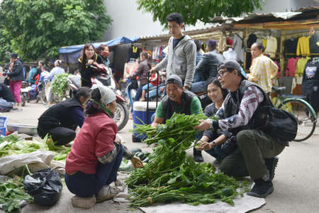 the merchant of venice: Ha Noi, Vietnam - December 3, 2015: Travellers are asking for buying green vegetables on a street market in Vietnam