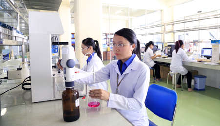 Long An, Vietnam - January 7, 2016: Experts are working in a veterinary medicine lab to produce vaccine for animals Editorial