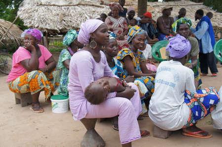 Casamance, Senegal - 1 augustus 2015: Vrouwen bijwonen van de infosessie. Zij zijn degenen in beheert de ontvangen materialen. Berichten worden rechtstreeks aan hen gericht om afval in een tijd van de voedselcrisis te voorkomen.