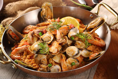 Pan of fried rice with clams, oysters and shrimps
