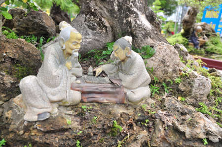 philosopher: Statues of Confucius philosopher are playing chess