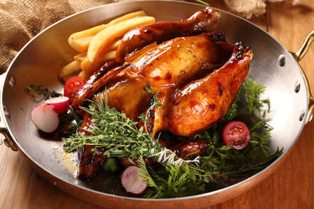 Fried chinese chicken in pan with herbs, potato and onion on the table