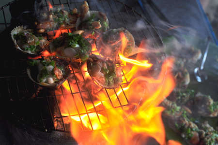 noix saint jacques: Grilling shellfish and seafood on hot fire Banque d'images