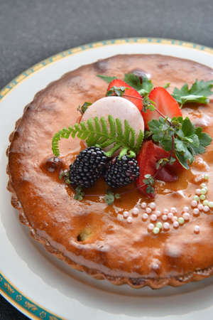 Special cake with blackberry and strawberry on white plate in restaurant Stock Photo
