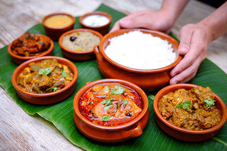 Indian meal with braised pork, curry and plain rice on banana leaf tray Standard-Bild