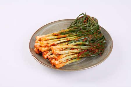 Korean green onion kimchi on plate on white background