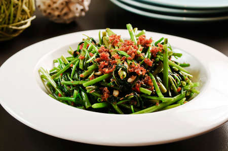 Fried vegetables of the morning glory or rau muong on white plate in Vietnam