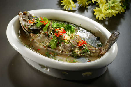 Special braised grouper fish with soup in chinese style in white big bowl on the table in restaurant Stock Photo