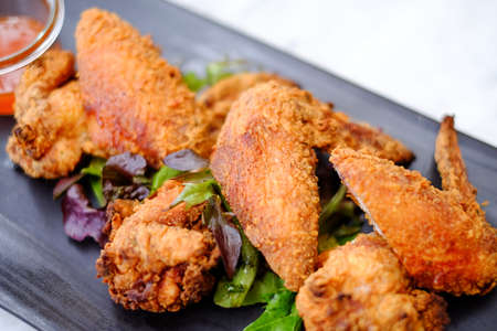 combo: Fried chicken wings on black plate in restaurant