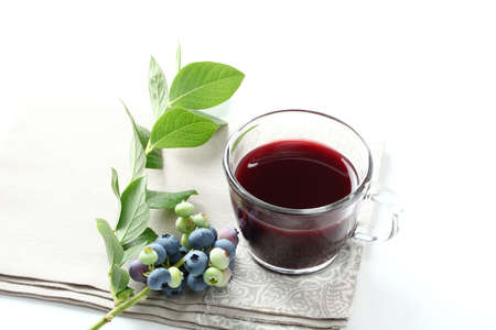 Blueberry juice with raw fruit and tea cup on white background Zdjęcie Seryjne