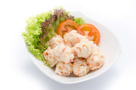 Lobster balls with tomato and herbs on white bowl