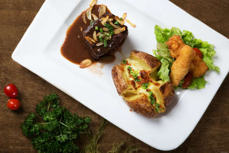 stewing: Stewed beef and fried fish with potato on white dish Stock Photo