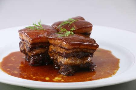 하얀 접시에 허브와 함께 중국 스타일의 찐된 돼지 고기