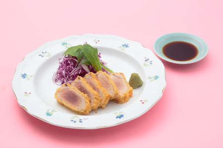 Fried breaded tuna with salad, wasabi and soy sauce on white background