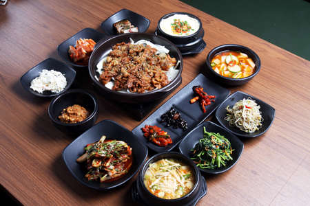 black dish: A traditional korean tray meal on wooden table Stock Photo