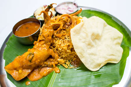 Indian meal with curry squid and fried rice on banana leaf tray Stock Photo