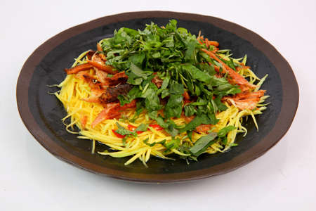 Mango salad with dried minced snake head fish in Mekong style on black plate