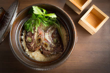 fish head: Braised fish head with rice in pot on the table Stock Photo