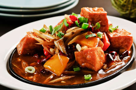 Braised tofu with onion and sauces on white plate Stock fotó