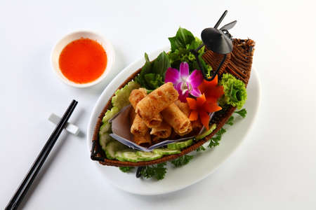 nem: Vietnamese fried spring rolls on bamboo tray with sliced cucumber, salad and chili sauce