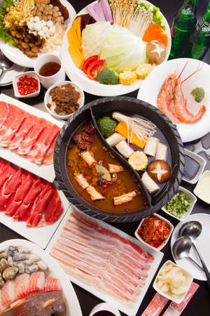 A special hot pot in Chinese style with beef, pork, seafood, mushroom, vegetables, shrimps and herbs Stockfoto