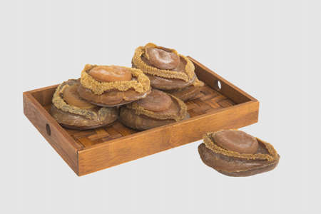 dried food: Dried abalone on bamboo tray in white background