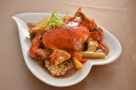 pincers: Fried crab in Singapore style on white plate in restaurant