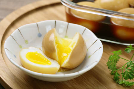 Runny eggs on white bowl with braised eggs on wooden table Archivio Fotografico