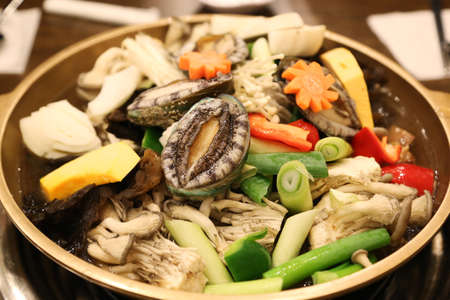 Abalone hot pot called the nobility of the sea with mushroom, pumpkin, carrot and herbs