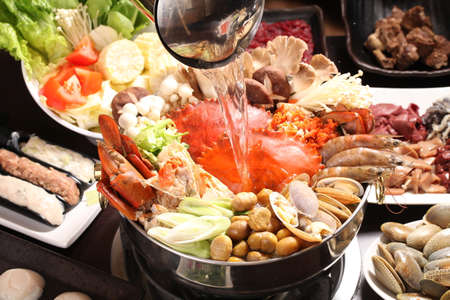 Supper crab hot pot with mushroom, clams, shrimps, corn and vegetables in Japanese stew