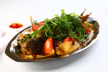 Steamed barramundi fish with onion and herbs in Hong Kong style Imagens