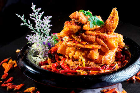 stirred: Special spicy fried crab in Chinese style on black plate