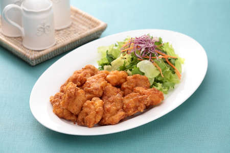 Sunsal fried Chicken Take Ake with salad on white plate with tea cup on the table