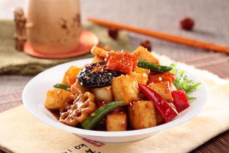 Tofu de raíz de lima hervida a fuego lento con champiñones, ají y rodajas de loto en un plato blanco