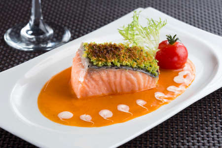 Baked Salmon filled with herbs in Lobster sauce and tomato, lettuce on white plate