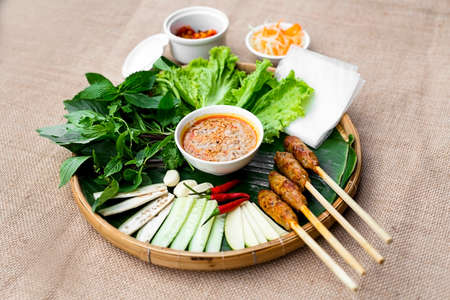 nem: Vietnamese fermented pork roll or nem Hue with lettuce, herbs and chili sauce on bamboo tray  Vietnamese fermented pork roll