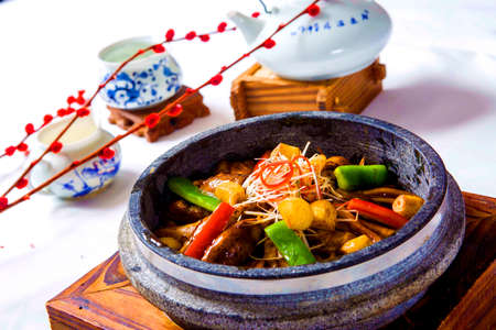 Freshwater eels braised with chili, vegetables and herbs in chinese stew with tea pot on wooden table