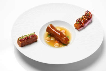 Sauteed pork foot with sauces on white plate in restaurant Stock Photo