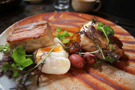 Poached eggs on the pork belly and the braised baby potatoes resting below nasturtium aioli added Stock Photo