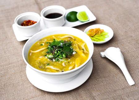 chili sauce: Vietnamese clams porridge in white bowl with lemon and chili sauce Stock Photo