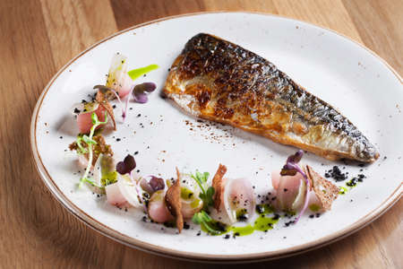 Fried mackerel with radish and shallots on white plate Stock Photo