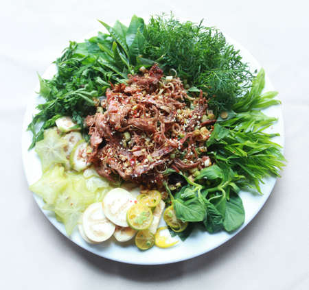 Vietnamese dried buffalo shredded meat with herbs and vegetables on white plate