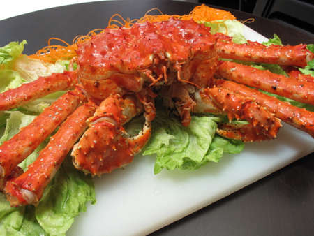 Fried red king crab with lettuce on white plate in restaurant Stock Photo