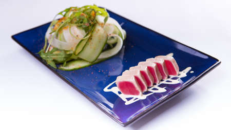 Salad with tuna tataki on blue chinese plate on white background